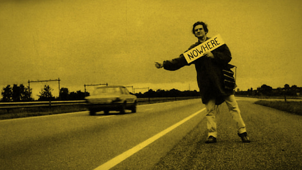 """Man hitchhiking on road with a sign that says """"Nowhere"""""""