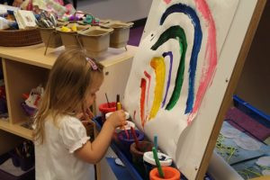 preschool girl painting a rainbow