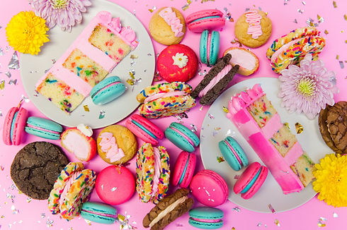 Colorful macarons, cookie sandwiches, and cake on pink background