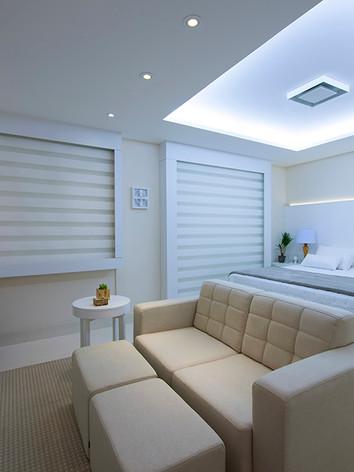 A arquiteta Tina Sanches projetou para o ambiente quarto de casal com destaque para a bancada de trabalho em Laca Fosca Branca e painel de cabeceira com os criados.