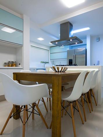 A arquiteta Tina Sanches projetou para a cozinha um espaço de socialização da família e amigos com destaque para o armário de eletrodomésticos  e com acabamento clean e as portas em perfil de alumínio natural e  vidros leitoso.