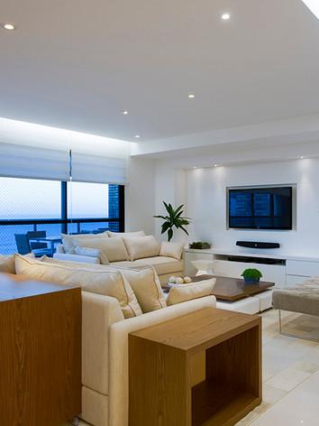 A arquiteta   Tina   Sanches   idealizou   sala   de   estar   e   TV   vista   de   outro   ângulo,   com destaque para Madeira Carvalho e Laca Fosca Branca.