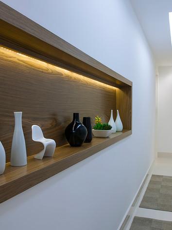 A   arquiteta   Tina   Sanches   projetou   para   o   ambiente   de   circulação   um   nicho   com iluminação embutida dando destaque o veio da madeira natural.