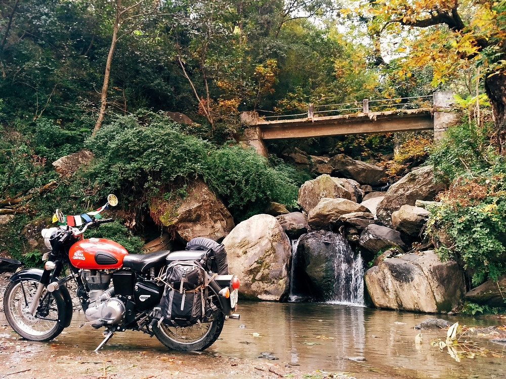 Red motorcycle, parked in front of small waterfall. Old bridge and trees changing to autumn leaves in background