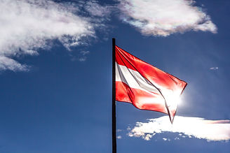 Waving flag of Austria backlit by the su