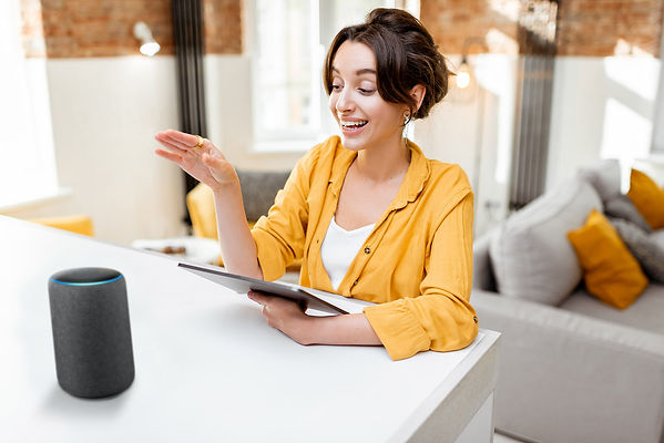 Women controlling her home appliances using Alexa Echo with Wozart devices.