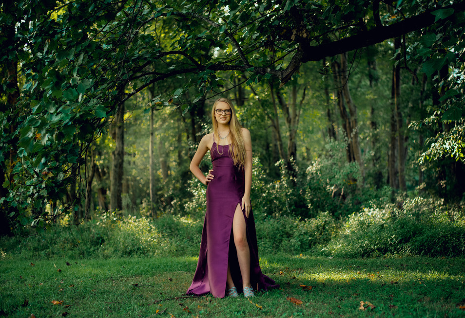 senior with purple dress in forest