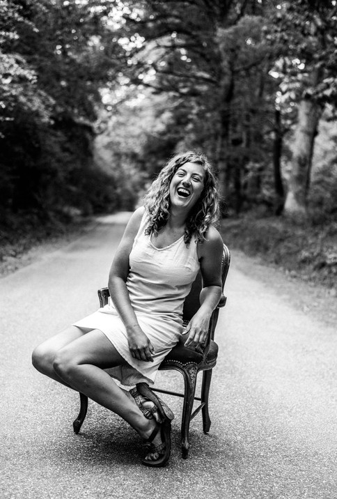 portrait in vintage chair in middle of road bw