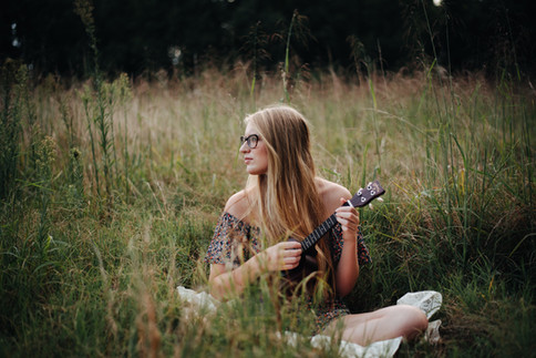 senior in field playing ukelele