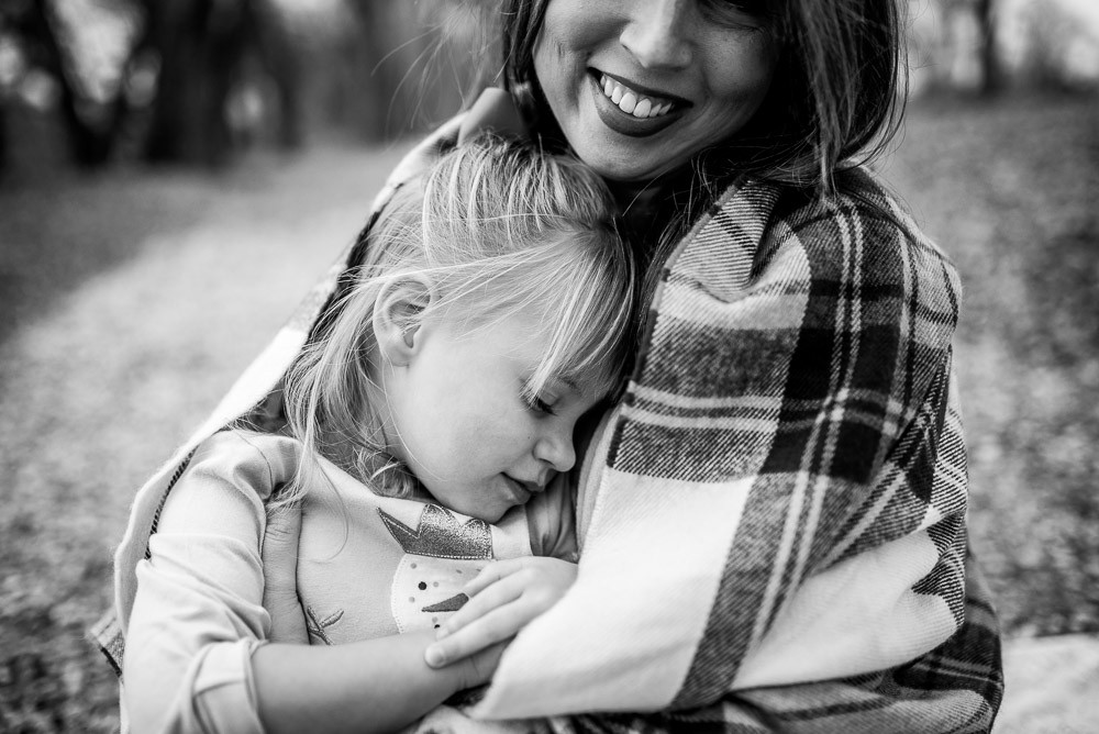 girl wrapped in mothers arms