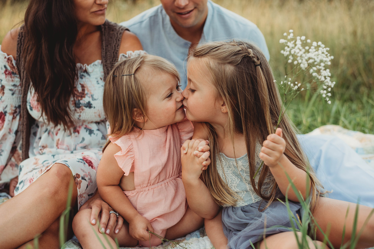 family portrait with kissing siblings