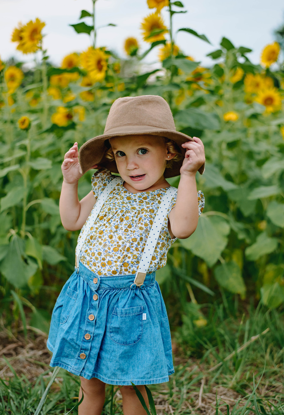 girl with hat and suspenders in sunflowe