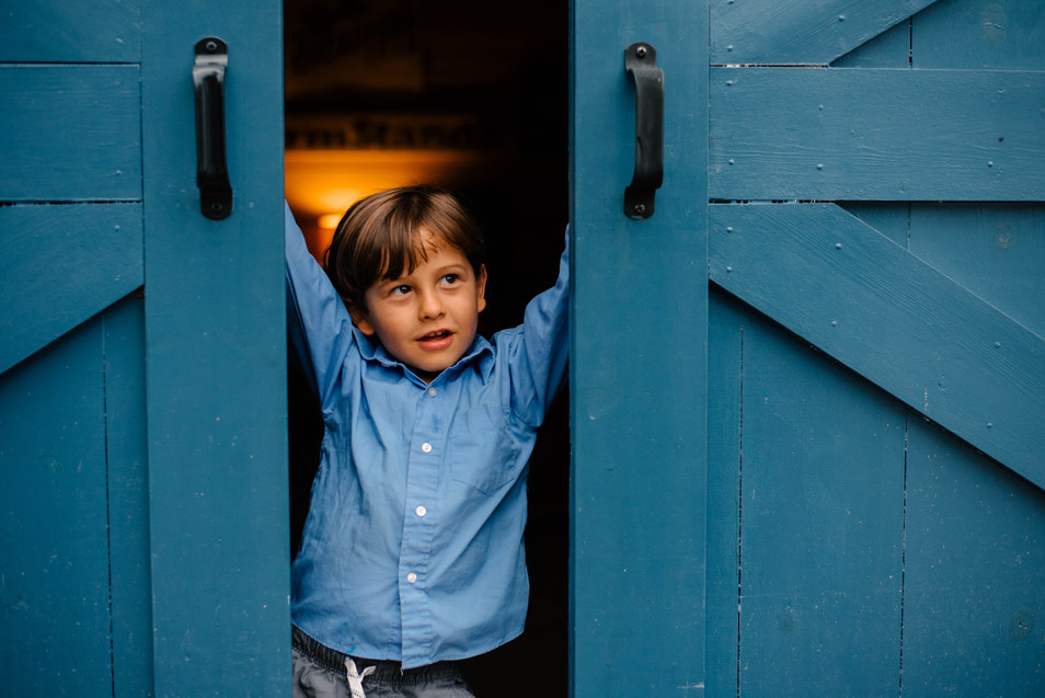 boy in front of bue barn door at Broadfork Farm