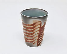 A slipcast porcelain cup with a trailed