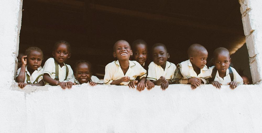 School kids from Nyumbani peering out of window