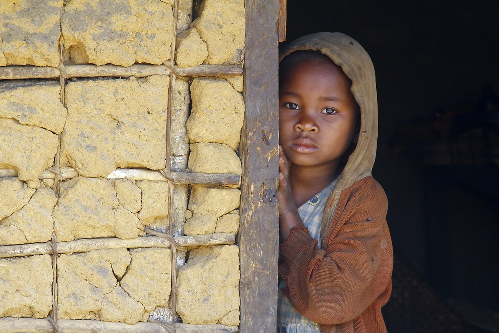 African girl looking out of hut