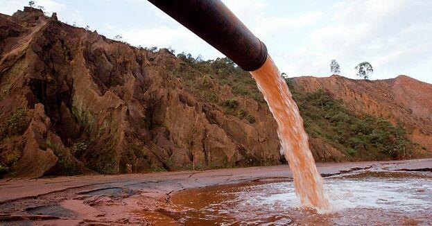Rejeitos industriais sendo despejados em uma fonte de agua que era limpa, contaminando-a.