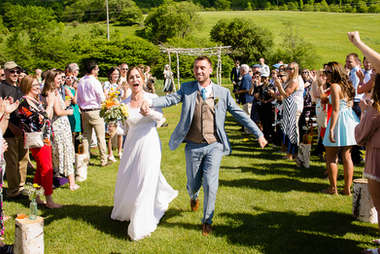 Bride and groom running down the aisle at the Maple Shade Farm in Delhi New York