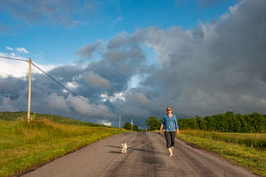Woman and pug walking down a county road with dramatic clouds and ble sky in Andes New York