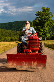 Bearded man on a red tractor in The Catskills