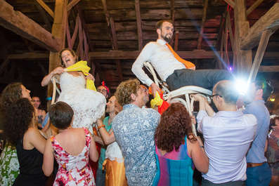 Bride and groom on chairs during a hora at Blenheim Hill Farm in the Catskills