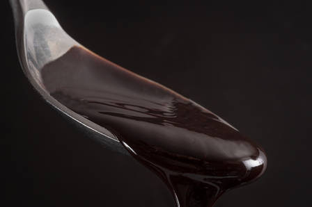 Chocolate syrup on a spoon