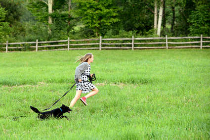 Young girl running with a black dog in Andes New York