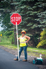 Woman road worker holding a shop sign on a county road in Roxbury New York