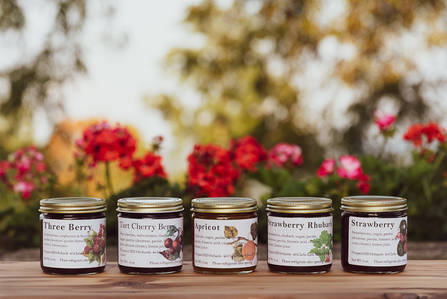 Jars of jam on a wood table with flowers in the background in the Catskills