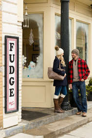 Attractive couple chatting in winter in front of a fudge store