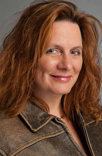Headshot of a woman with red hair on a gray background in the Catskills