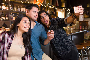 One woman and two men at a bar taking a selfie
