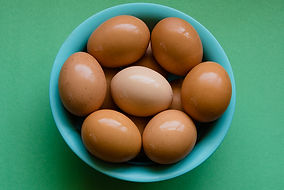 Brown eggs in a blue bowel on a green table