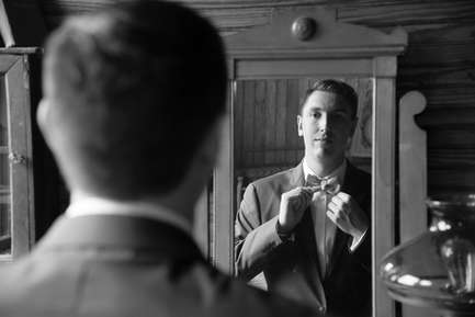 Groom adjusting his bowtie in a mirror in black and white
