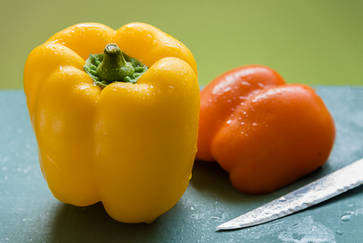 Yellow and orange peppers on a cyan cutting board