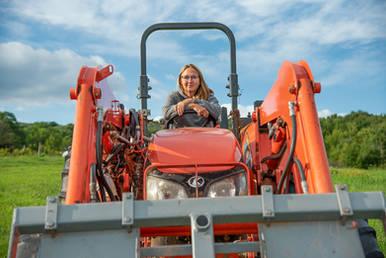 Woman on an orange tractor in Bovina New York