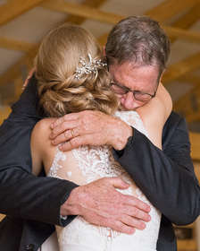 Father of the bride hugging his bride daughter on her wedding day at The Natural Gardens in The Catskills