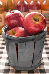 Apples in a basket with bottles in the background