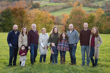 Family posing with fall colors and mountain in the background
