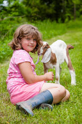 Girl with a pet goat sitting on the grass