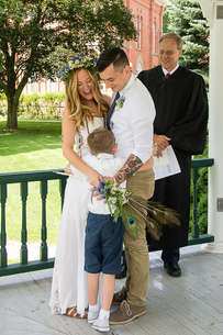Bride and Groom and child hugging during a wedding ceremony in Delhi New York in The Catskills