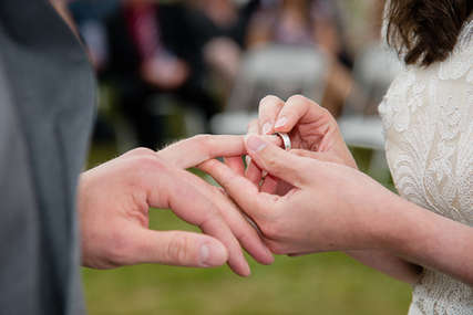 Bride putting wedding ring on groom in the Catskill Moutains
