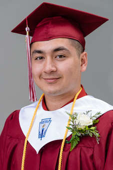 Headshot of a high school graduate with a cap and gown on a grey background at the Andes Central School