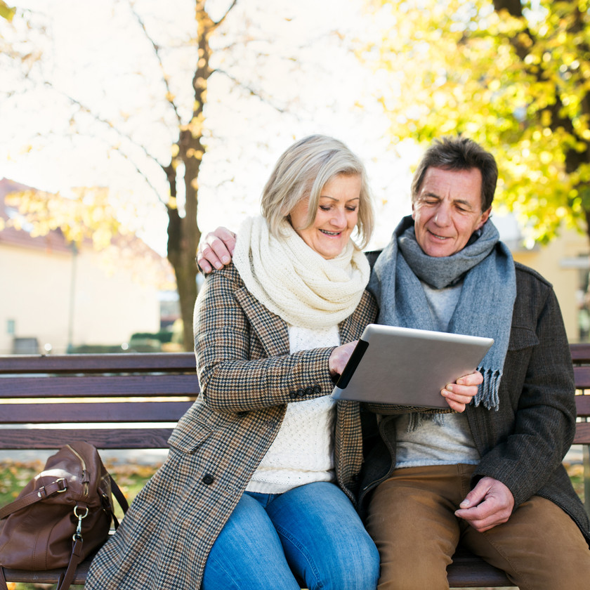 couple sitting on bench outside with tablet