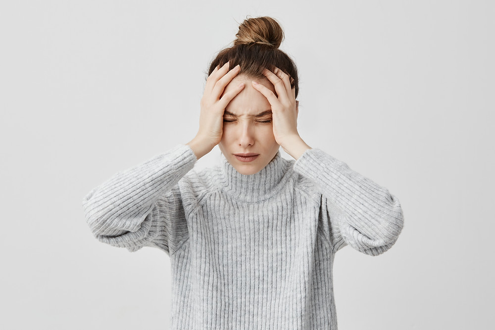 woman with a headache holding her forehead
