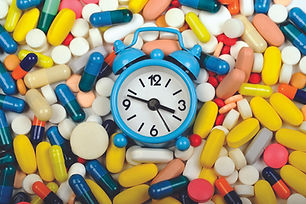 Blue clock surrounded by multi-colored pill capsules