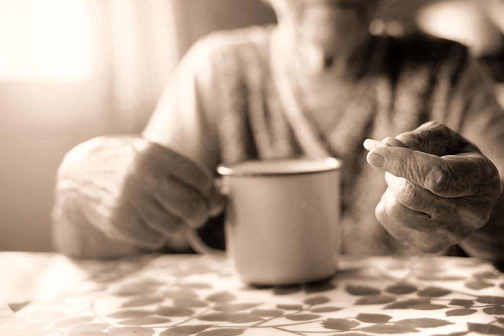 senior woman at table with coffee and a pill