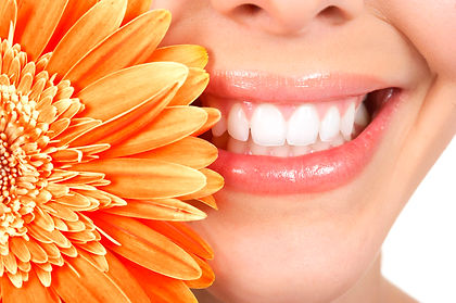 womans teeth smiling next to orange flower