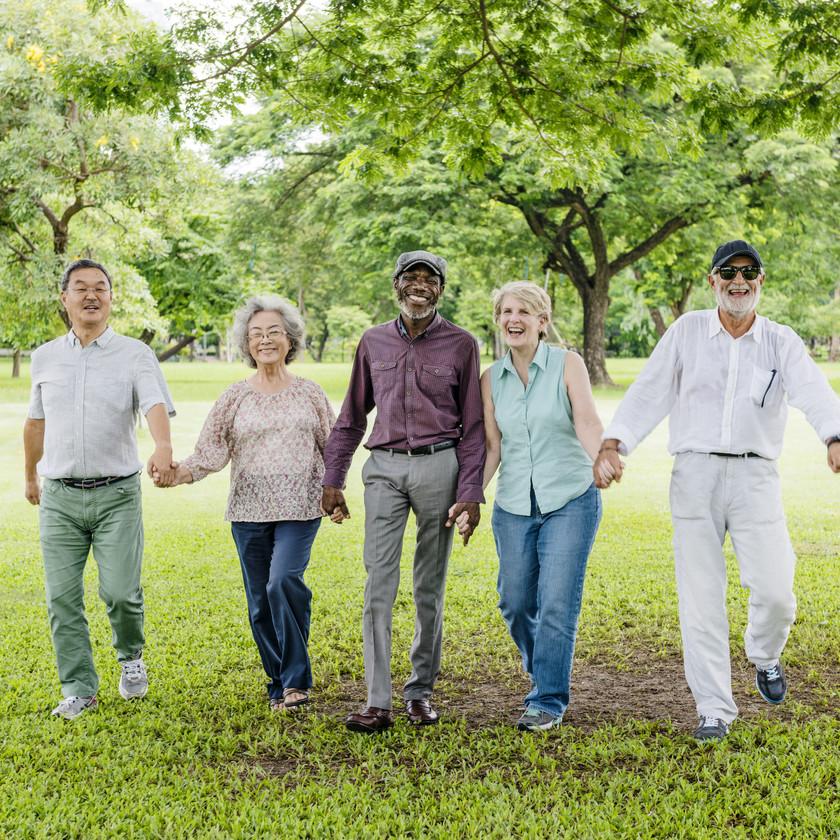 group of elderly individuals holding hands walking