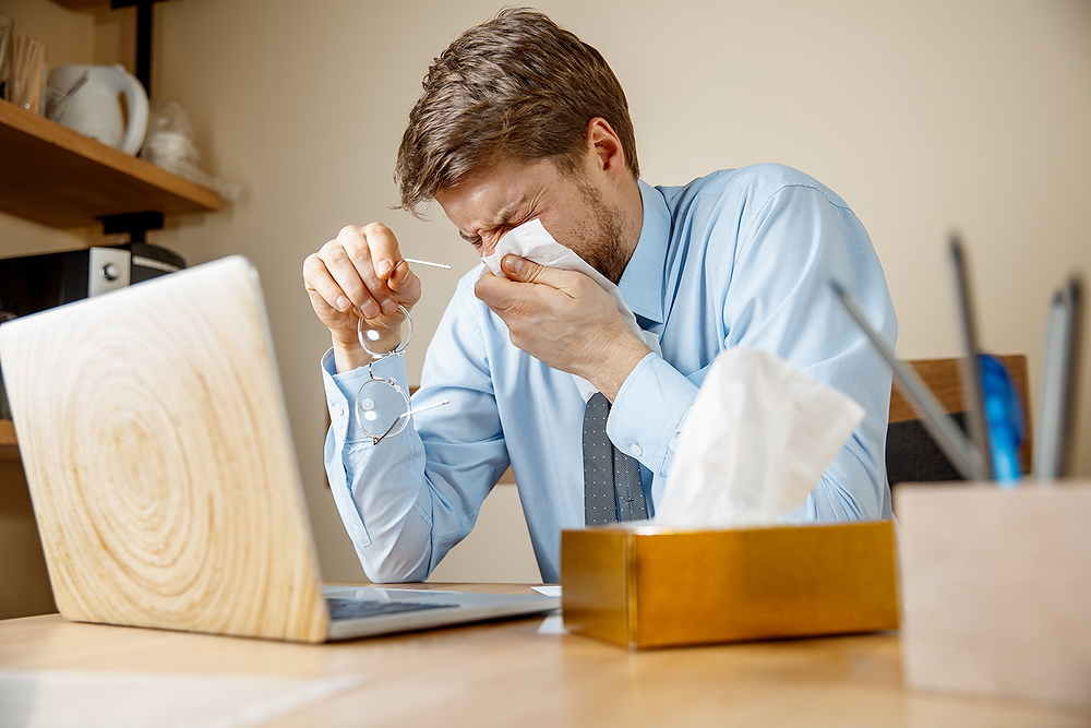 Man that is sneezing into a tissue at his desk
